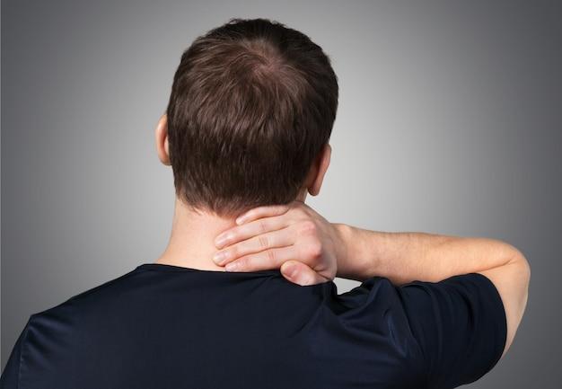 Мужчина держит больную шею на фоне, вид сзади