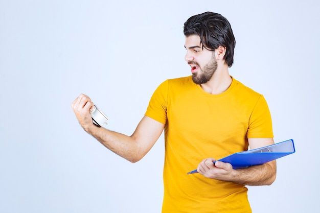 Man holding an alarm clock and a blue folder.