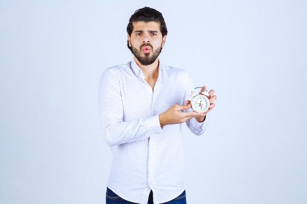 Uomo con in mano una sveglia e confuso perché è in ritardo