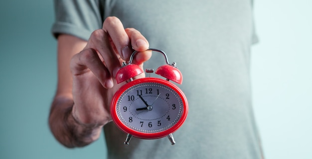 A man holding an alarm clock in his hand