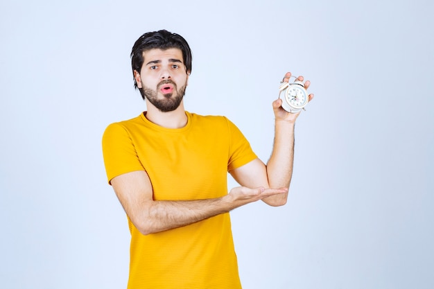 Man holding an alarm clock and looks amazed.