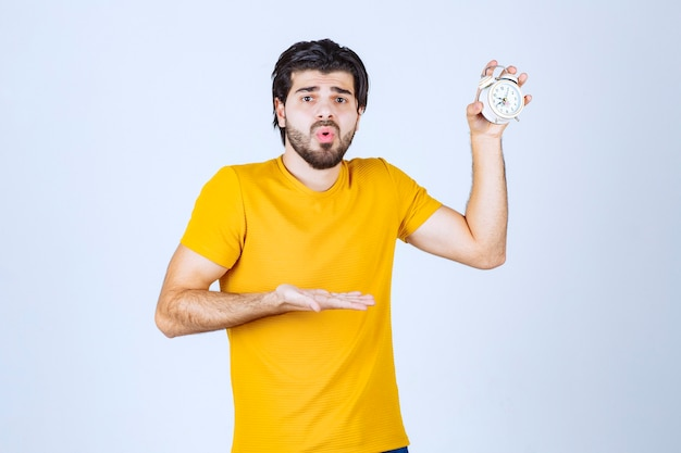 Man holding an alarm clock and looks surprised.