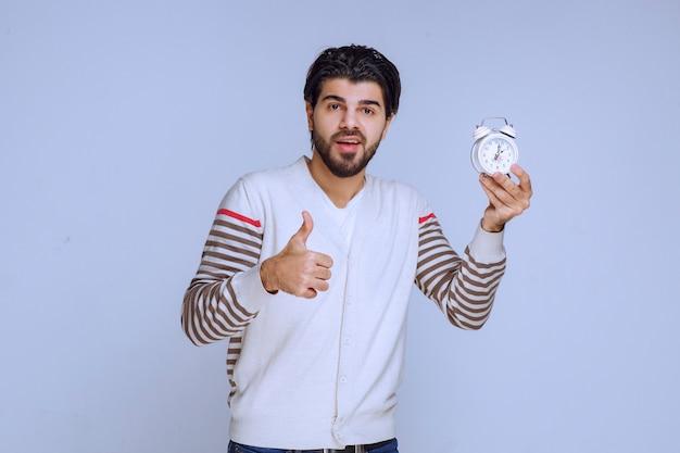 Man holding an alarm clock and making thumb up.