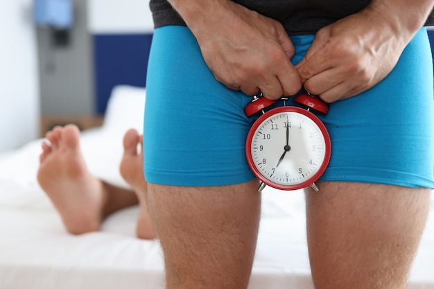 Man holding alarm clock near genitals against background of lying female legs closeup. male reproductive health problems concept