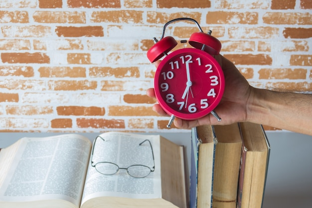 A man holding alarm clock above open books , reading time