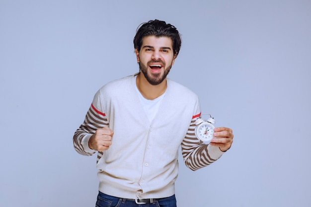Man holding an alarm clock and showing that it works well and enjoying.