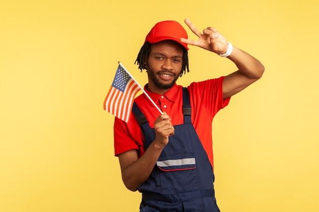 Man holding american flag and showing peace gesture with fingers looking at camera