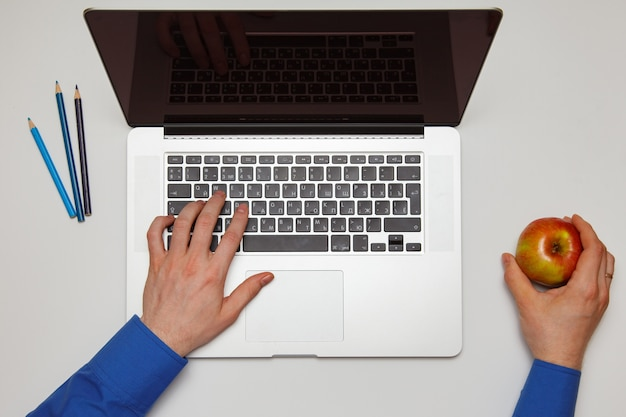 Мужчина держит яблоко и печатает на ноутбуке