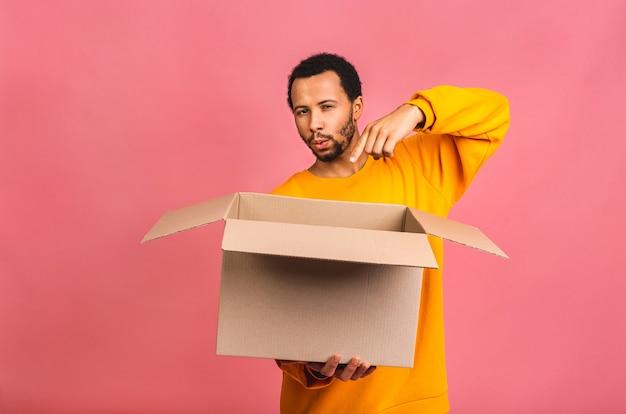 Человек, держащий пустую коробку, изолированную над розовым. концепция доставки.