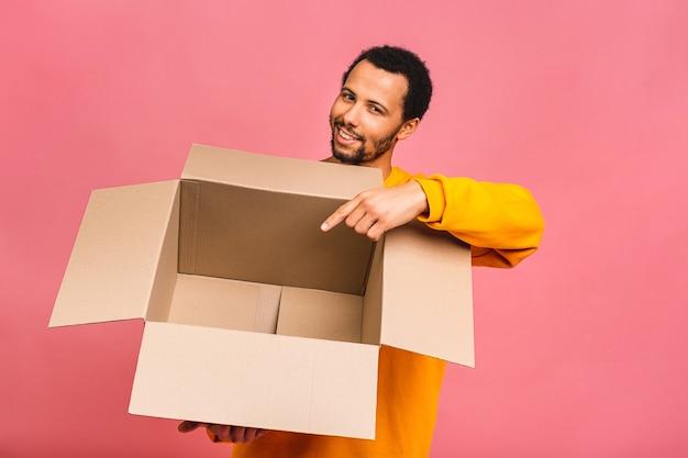 Мужчина держит пустую коробку, изолированную над розовым
