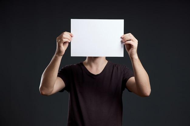 手に空の紙シートを持っている男