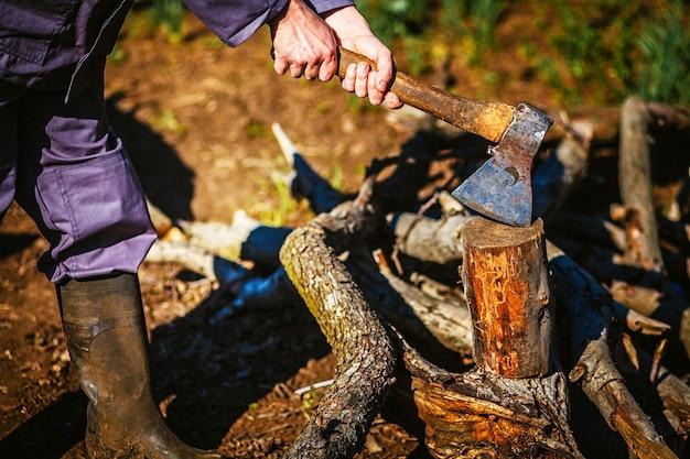 Мужчина держит промышленный топор и режет дерево