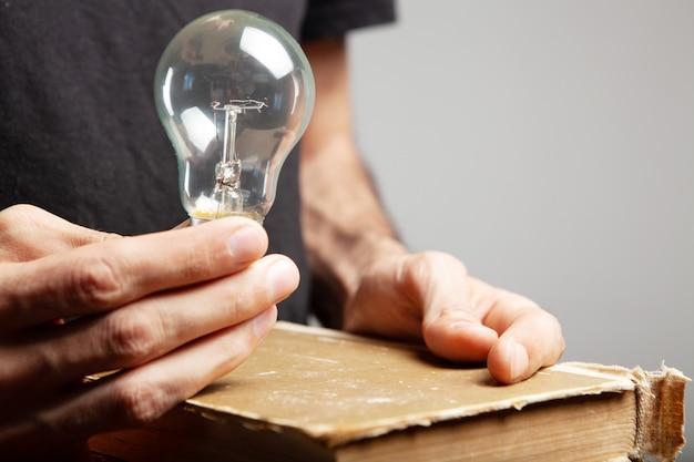 펼친 책과 전구를 들고 남자. 책에서 개념 아이디어
