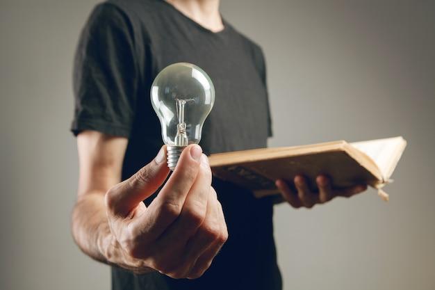 Мужчина держит открытую книгу и лампочку. концептуальная идея из книги