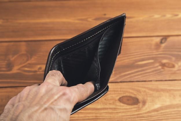 Мужчина держит открытый пустой кожаный бумажник