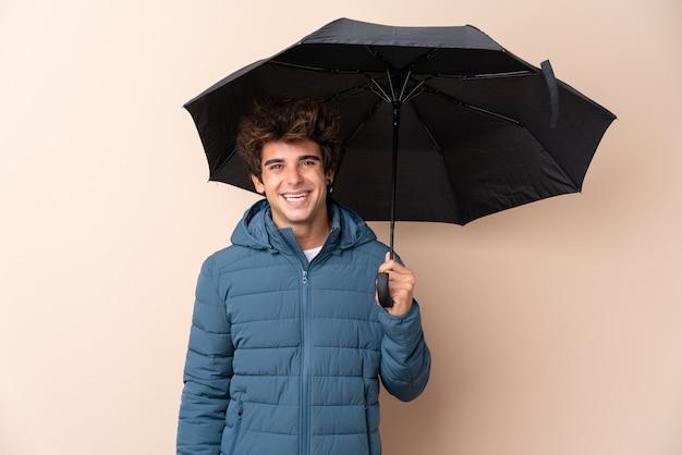 Мужчина держит зонтик над изолированной стеной, много улыбается