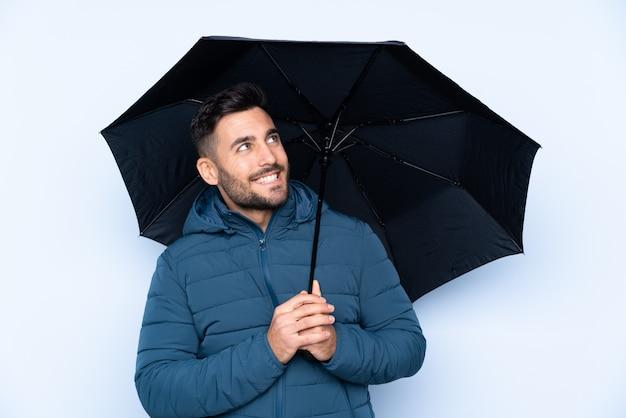 Мужчина держит зонтик над изолированной стеной с счастливым выражением
