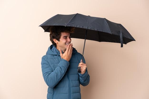 Мужчина держит зонтик над изолированной стеной с удивлением и шокирован выражением лица