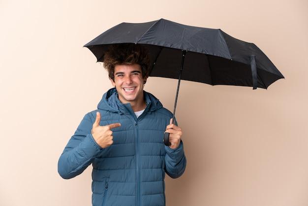 Мужчина держит зонтик над изолированной стеной с удивленным выражением лица