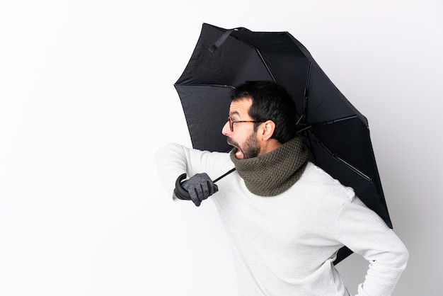 孤立した壁に傘を持って男