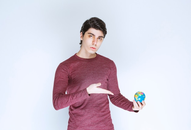 Мужчина держит и демонстрирует мини-глобус земли.