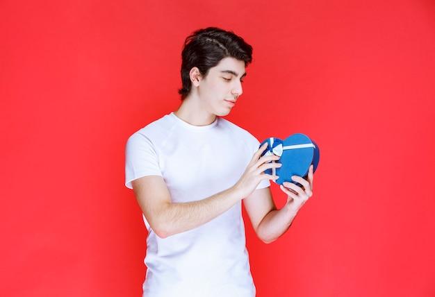 남자 보유 및 심장 모양 파란색 선물 상자를 제공합니다.