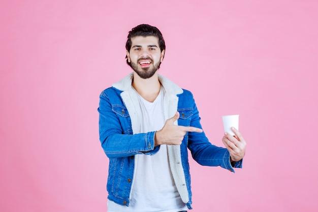 Мужчина держит и представляет новую одноразовую кофейную чашку