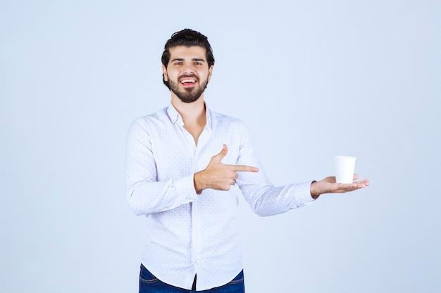 Мужчина держит и продвигает чашку кофе или кофе