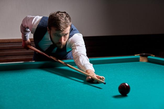 당구 테이블에 팔을 잡고 스누커 게임을하거나 풀 공을 쏠 준비를하는 남자. 스포츠 게임 스누커 당구