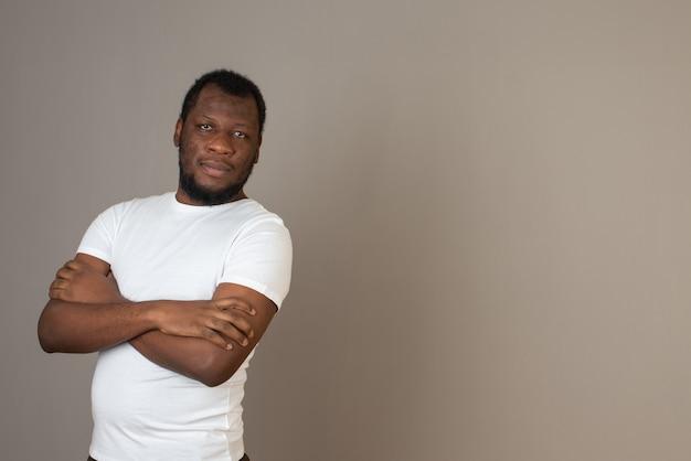 腕を組んで、灰色の壁の前に立っている男 無料写真