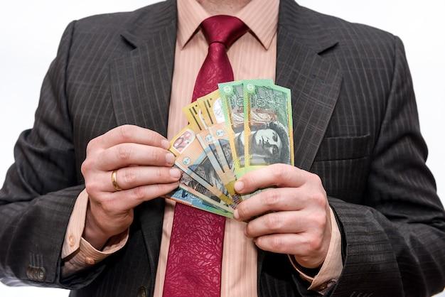 호주 달러 지폐를 들고 남자를 닫습니다.