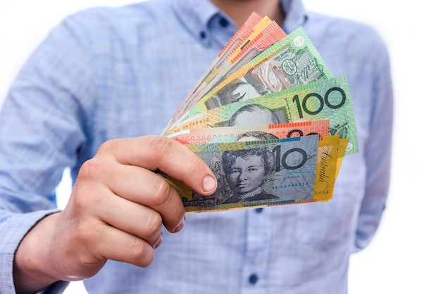 白で隔離されるオーストラリアドル紙幣を保持している男