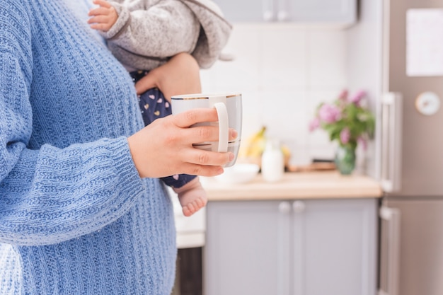 Man holding baby and mug in kitchen
