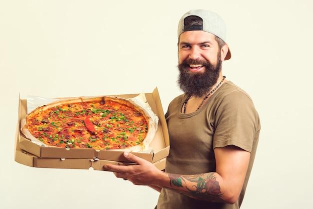 手においしいピザと天板を持っている男