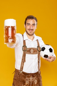 Man holding a ball and beer pint