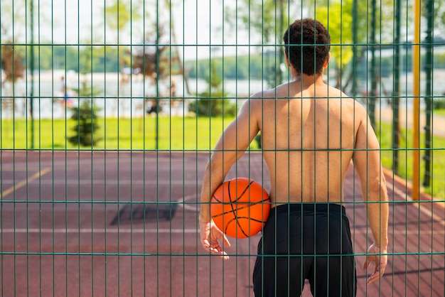 Man holding a ball and looking at hoop
