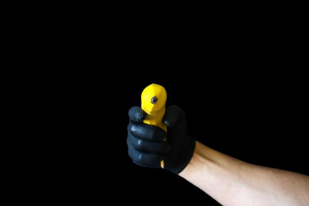 Человек, держащий банан в черных перчатках. использование фруктов как оружия.