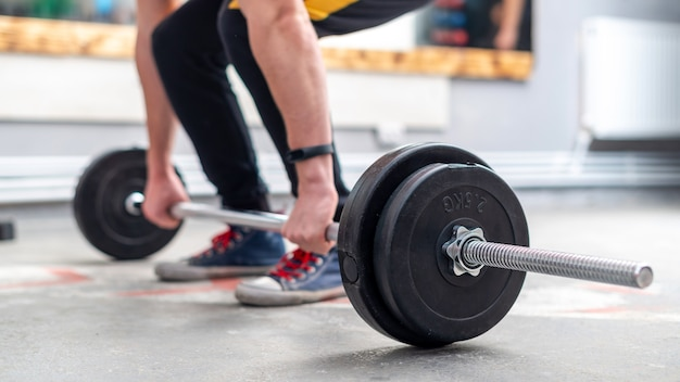 A man holding a barbell on the floor in the gym