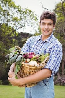 Man holding a basket of freshly harvested vegetables in garden
