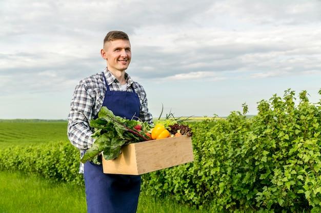 Мужчина держит корзину с овощами на ферме