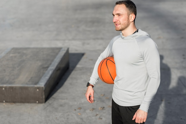 Man holding a basketball and looking away