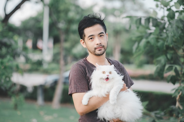 Man holding a beautiful furry persian cat in the park