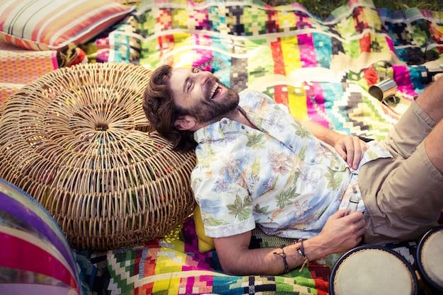 Мужчина держит бутылку пива и отдыхает на плетеной табуретке в кемпинге