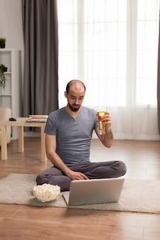 ノートパソコンで友達と話している間、ビアグラスを持っている男。