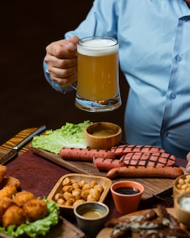 Мужчина держит пивную кружку, подается с жареными колбасками, нутом, хрустящими фрикадельками