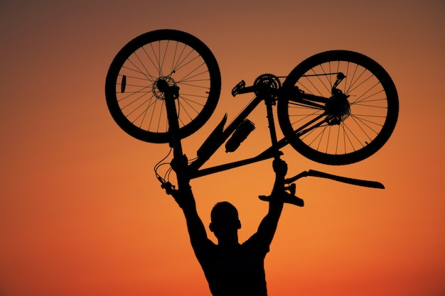 Man holding a bicycle against the sunset background
