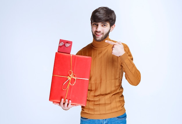 大小の赤いギフトボックスを持って、それらをデモンストレーションする男。