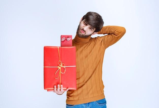 Мужчина держит большие и маленькие красные подарочные коробки и предлагает их своей девушке.