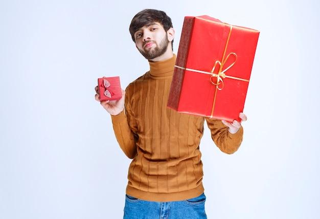大小の赤いギフトボックスを持って、そのうちの1つをガールフレンドに提供している男性。