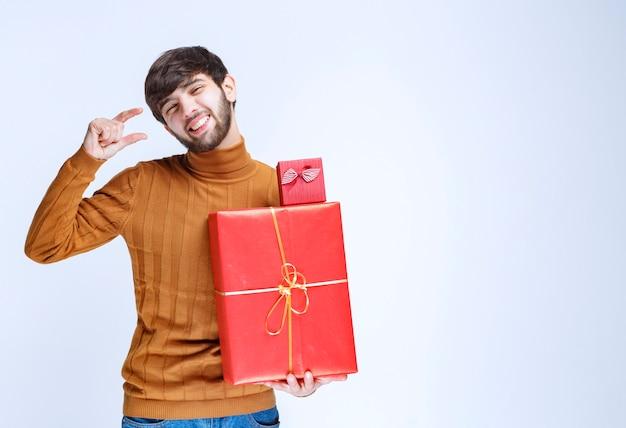 Мужчина держит большие и маленькие красные подарочные коробки и показывает размер в руке.